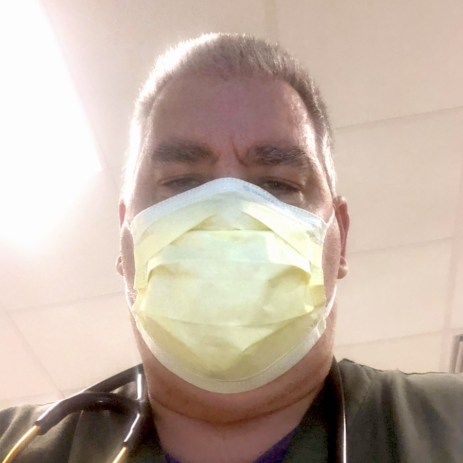 Timothy working as a respiratory therapist, wearing a mask