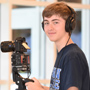 Student smiling holding camera equipment